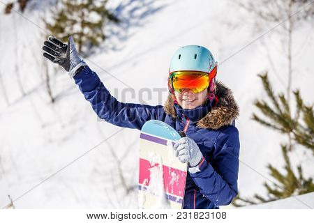 Portrait Of Smiling Female Athlete Wearing Helmet With Snowboard On Blurred Winter Day Background