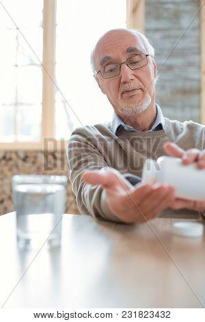 Blood Pressure Medication. Handsome Nice Senior Man Sitting On Blurred Background While Placing Pill