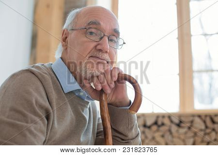 One More Minute. Nice Handsome Senior Man Looking At Camera While Leaning On Cane And Wearing Glasse