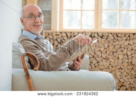 Pleasant Time Spending. Appealing Satisfied Senior Man Sitting On Couch While Holding Book And Smili