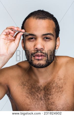 Pampering Time. Portrait Of Handsome Shirtless Young Black Man Looking At Camera And Pampering His E