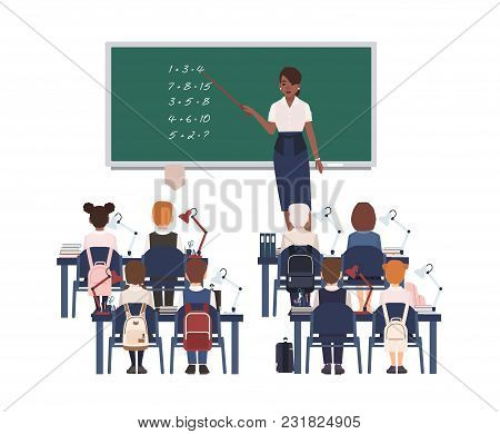 Female Math Teacher Explaining Summation To Elementary School Kids Or Pupils. Smiling African Americ