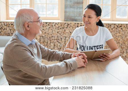 Social Volunteering. Merry Optimistic Volunteer Carrying Book While Talking To Senior Man And Lookin