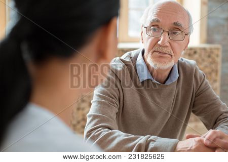 Social Interaction. Handsome Positive Senior Man Wearing Glasses While Listening To Volunteer And Po