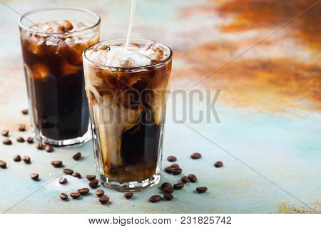 Ice Coffee In A Tall Glass With Cream Poured Over And Coffee Beans. Cold Summer Drink On A Blue Rust