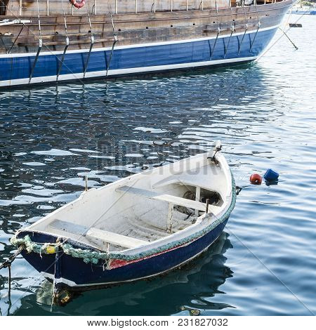 Yachts Docked At The Port Of Malta. A Shabby Old Boat Among The Luxury Ships