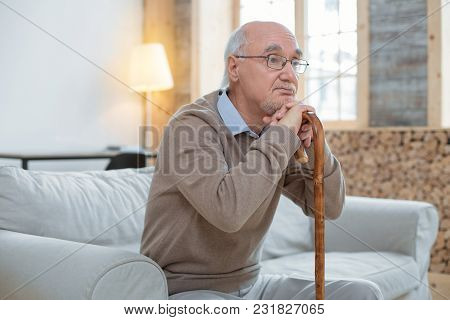 Bad Day. Attractive Thoughtful Senior Man Leaning On Cane While Wearing Glasses And Sitting On Couch