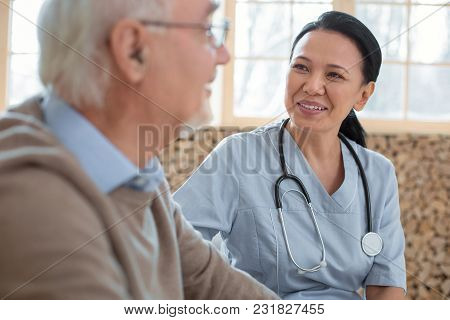 My Patient. Appealing Happy Doctor Wearing Uniform While Gazing At Senior Man And Smiling