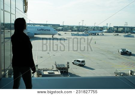 Frankfurt Am Main, Germany - October 11, 2015: Woman In Airport. Girl Silhouette Look At Planes On A