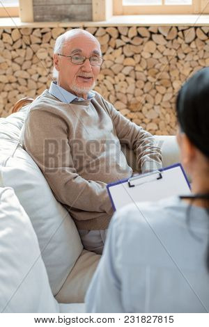 My Wellness. Top View Of Jovial Cheerful Senior Man Sitting On Sofa While Wearing Glasses And Sharin