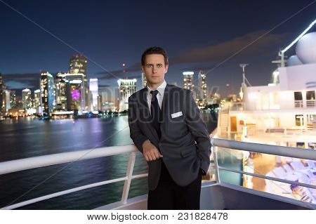 Man Steward On Ship Board At Night In Miami, Usa. Macho In Suit Jacket On City Skyline. Water Transp
