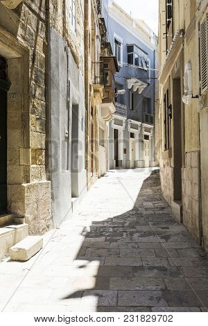 Typical Narrow Street On The Island Of Malta. Buildings With Traditional Colorful Maltese Balconies