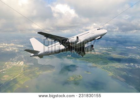 White Airplane Flying In The Sky Among Clouds Floating Over Land Surface. White Airplane In The Flig