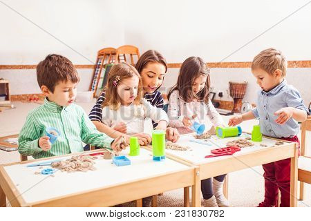 Teacher And Kids Play With Creative Kinetic Sand On The Table