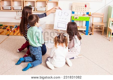 Beautiful Young Teacher Showing  And Explaining Figures Preschoolers, Children Sit In A Circle