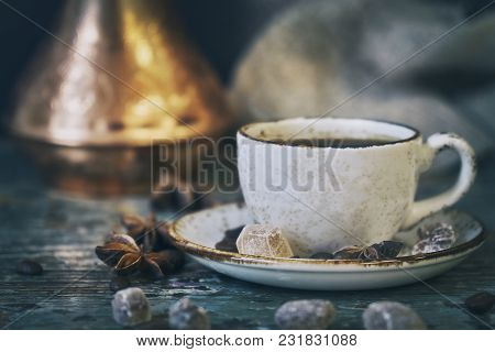 Still Life With Cup Of Coffee And Turkish Coffee Pot With Coffee Beans Lying On A Shabby Wooden Tabl