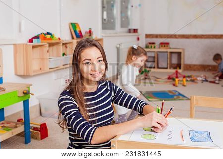 Smiling Young Preschool Teacher In A Kindergarten