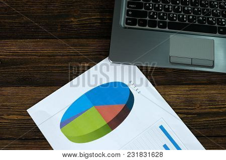 Notebook Laptop Computer And Financial Graph On White Paper On Working Table, Business Planning Visi