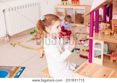 The Girl Is Playing With The Barby House In The Kindergarten While The Boy Is Playing With Other Toy