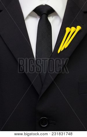 The Detail Of Wedding Suit With Golf Design. Yellow Golf Tees On The Flap Of Black Jacket.