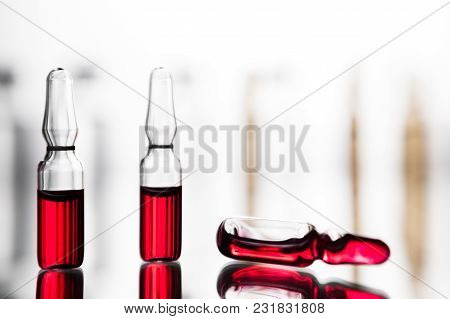 Ampoules With Red Liquid. On White Background Close Up. Group Of Ampoules With A Transparent Medicin
