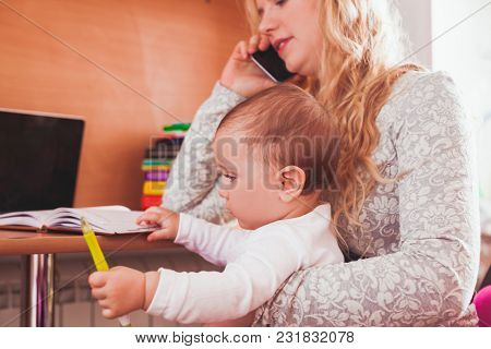Young Mother Working And Holding Daughter In Her Arms