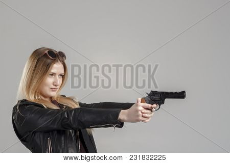 A Girl In A Leather Jacket Holds A Revolver In Her Hands, Danger, Self-defense. The Image Of A Confi