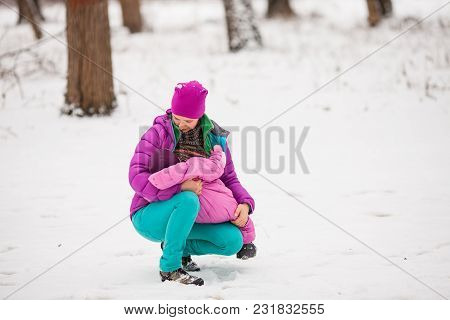 Breastfeeding Toddler Outdoor In Winter Park, Mom And Girl
