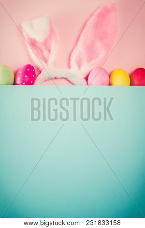 Easter Rabbit Ears And Colored Easter Colored Eggs On Pink And Blue Background With Copy Space, Retr