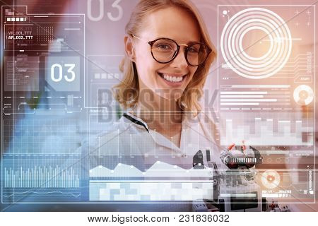 Good Mood. Cheerful Enthusiastic Positive Engineer Enjoying Her Working Day While Standing With A Li