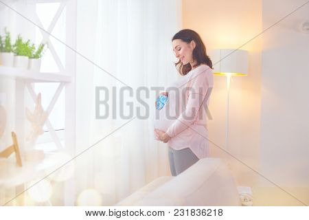 Pregnant Woman touching her belly and playing with little baby shoes. Happy Pregnant middle aged mother at home. Female holding  her tummy. Healthy Pregnancy concept, Parenthood poster