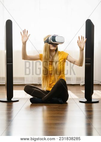 Young Woman Wearing Virtual Reality Goggles Vr Box With Arms Outstretched Sitting On Floor In Living
