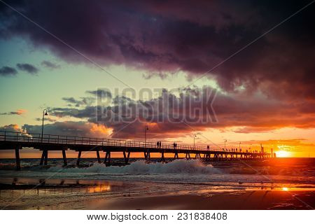 People Walking On Glenelg Beach Jetty At Sunset, South Australia