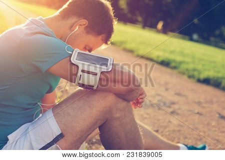 Young Athlete Sitting And Resting After Workout In The Park, Outdoors