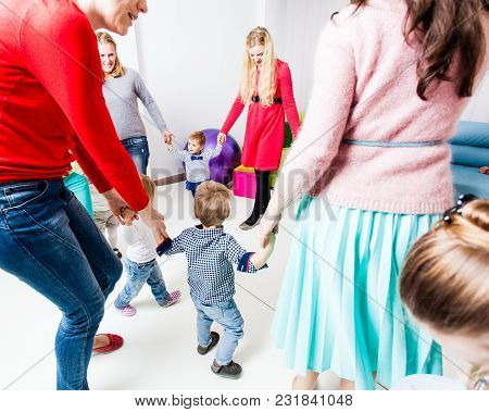 Round Dance Moms And Children. Moms And Their Children Hold Hands By Forming A Circle In The Kinderg