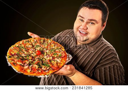 Fat man eating fast food and offers great pizza to customers . Male treats chic junk meal to friends. Breakfast for overweight person. leads to obesity. Use of harmful products.