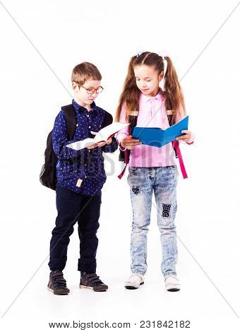 Pupils Boy And Girl Isolated On The White Background. Teenagers With Backpacks Holding The Copybooks