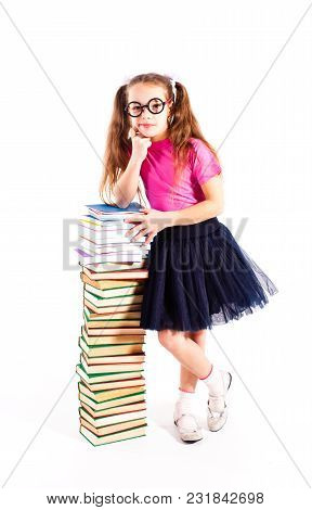 Cute Girl In Glasses Is Standing Close To Stack Of Books Isolated On White Background. Very Smart Pu