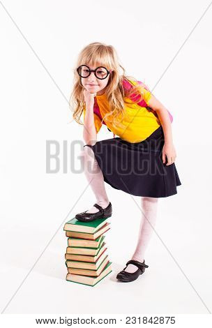 Very Smart Girl Kid In Glasses Stand With Book Heap. Girl With Backpack In Yellow T-short Isolated O