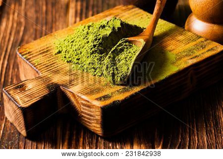 Matcha Powdered Tea Heap And Scoop On The Wooden Board