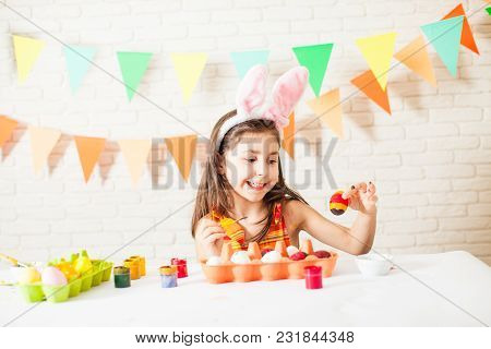 Girl With Easter Bunny Ears Is Painting Colorful Easter Eggs At Home. Easter Decorations And Prepara