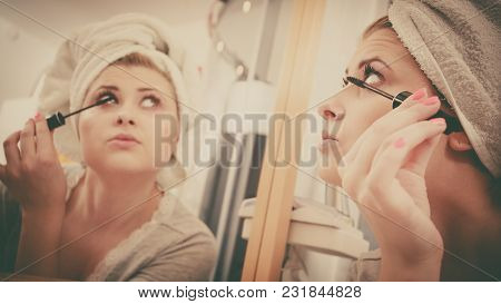 Visage And Make Up Concept. Woman In Bathroom Wearing Towel On Head Applying Mascara On Eyelashes