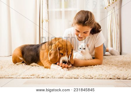 The Dog Is Licking Hand. The Girl Is Lying On The Carpet And Patting The Whita Cat