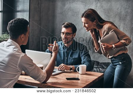 Mutual Understanding. Group Of Young Confident Business People Discussing Something While Spending T