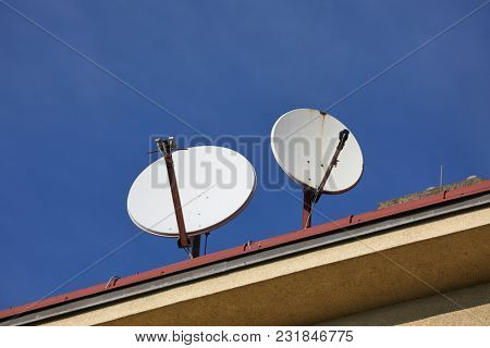 Parabola satellite receivers on a roof, pointed at the sky