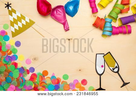 Colorful Confetti, Streamer And Party Hat As Decoration Lying On Wooden Background As Flatlay