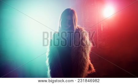 Trendy Young Woman In Club, Neon Light, Lots Of Smoke. Pink Fur Coat. Silhouette