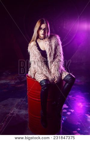 Young Attractive Woman With Stylish Clothes. Beautiful Girl In A Fluffy Pink Fur Coat Sits On A Barr