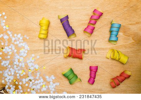 Colorful Confetti And Streamer As Decoration Lying On Wooden Background As Flatlay
