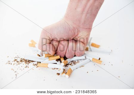 Quit Smoking Concept - Male Hand Crushing Cigarettes